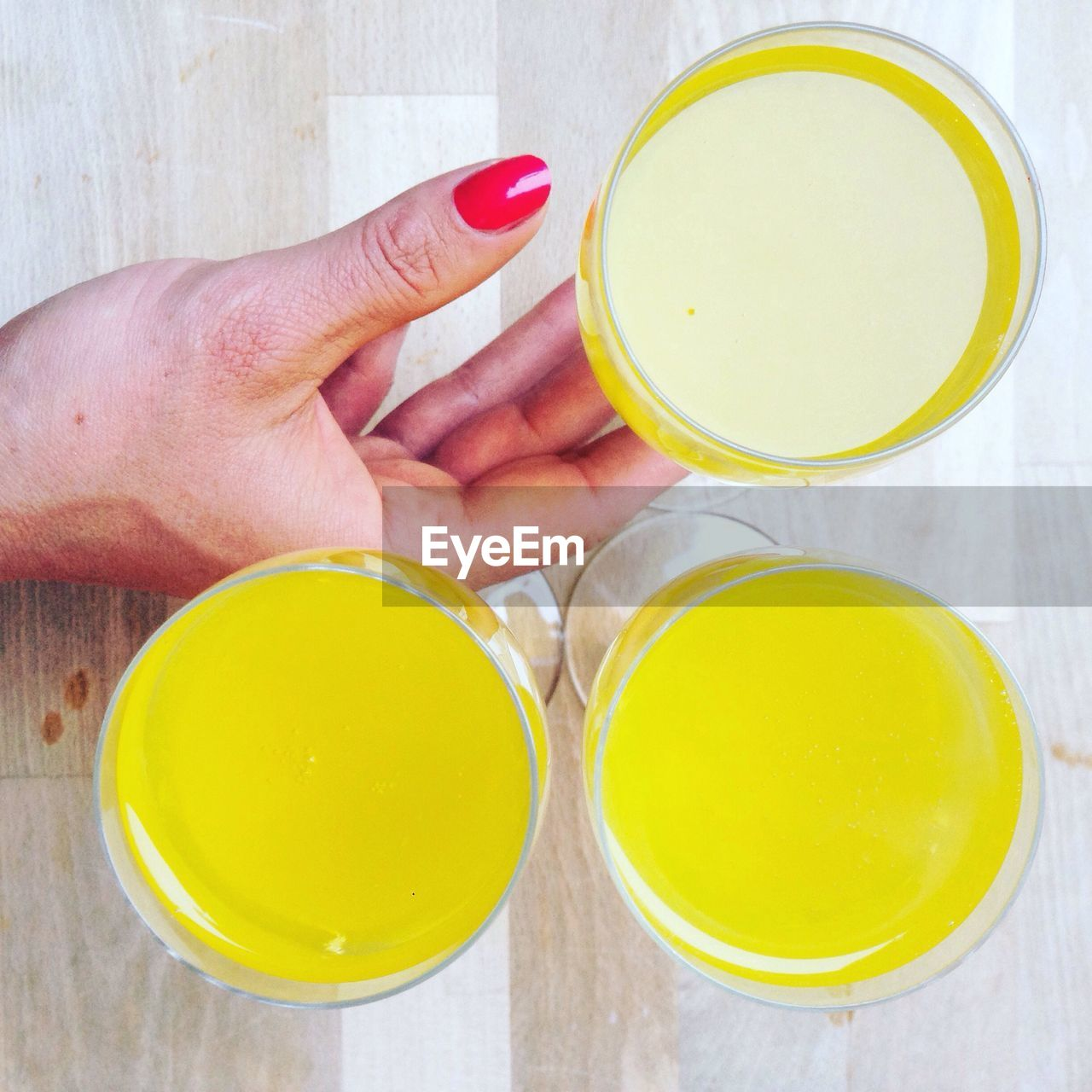 Midsection of woman with yellow drink on table