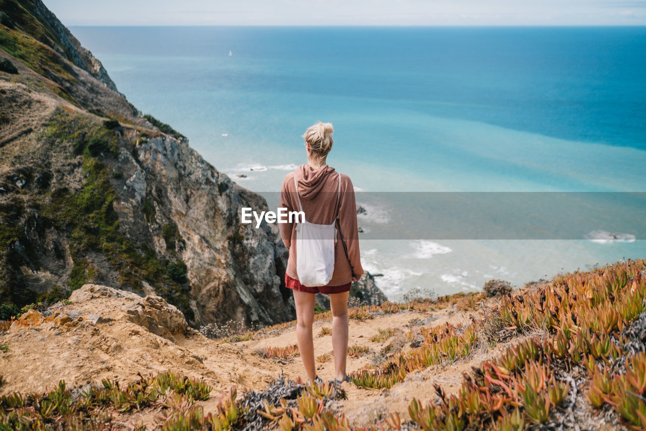 Rear View Of Woman Standing On Mountain Against Sea