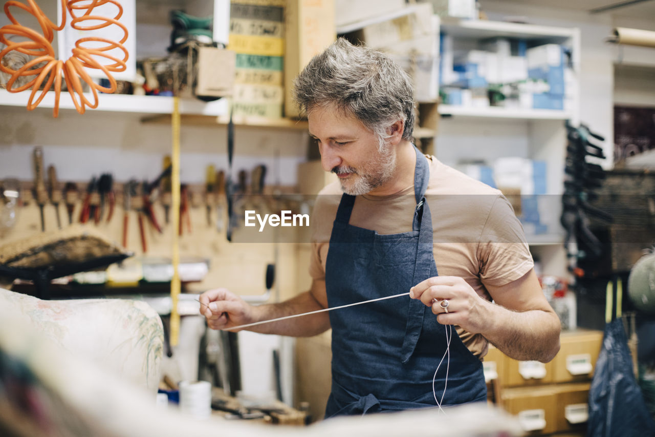 one person, workshop, real people, occupation, working, indoors, concentration, craft, art and craft, skill, front view, business, waist up, casual clothing, looking, holding, selective focus, accuracy, standing, preparation, workbench, effort