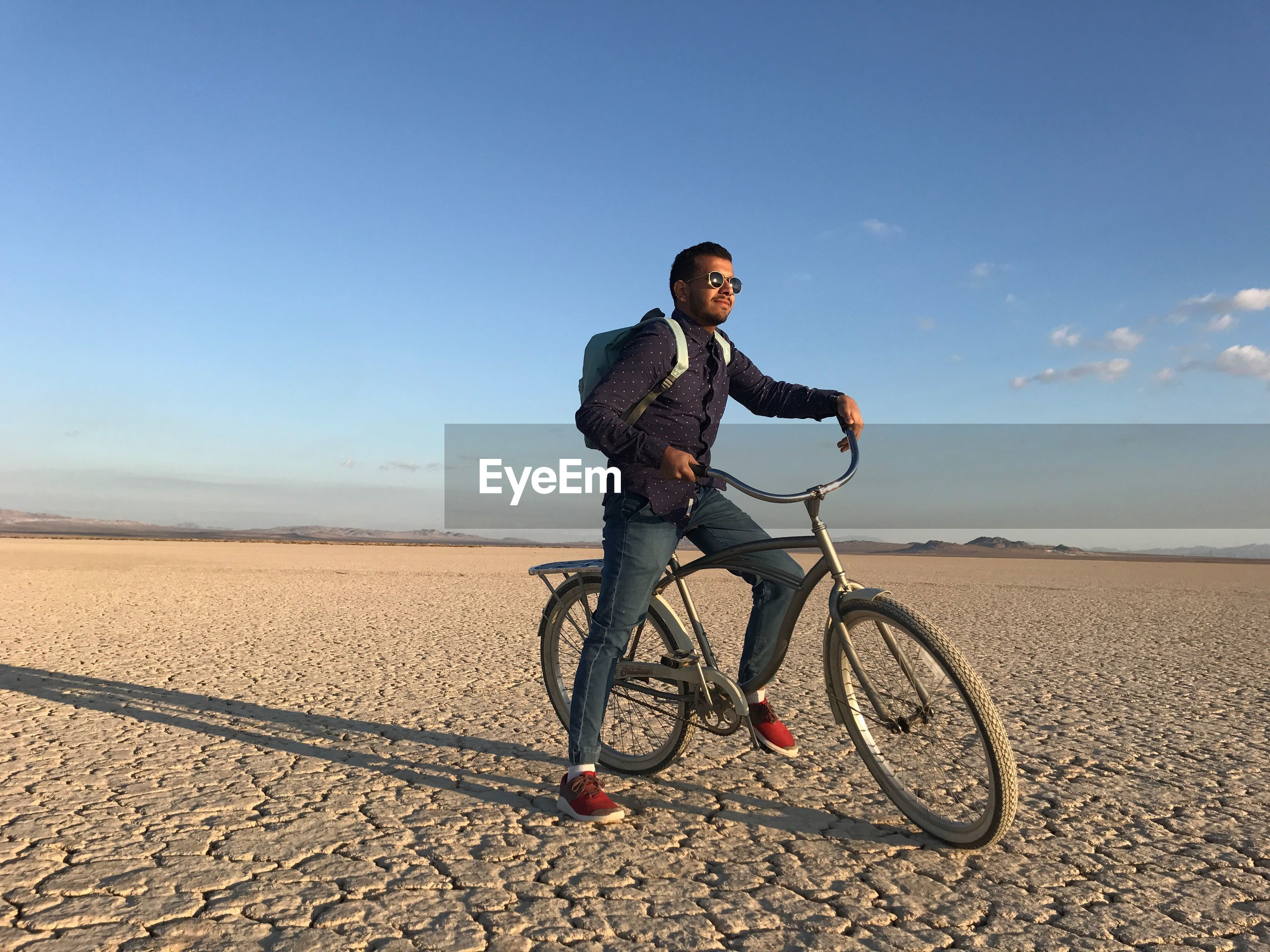 Full length of man with bicycle on landscape against sky