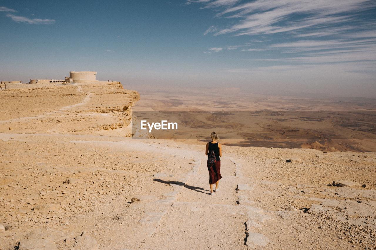 Rear view of woman walking on sand in desert against sky