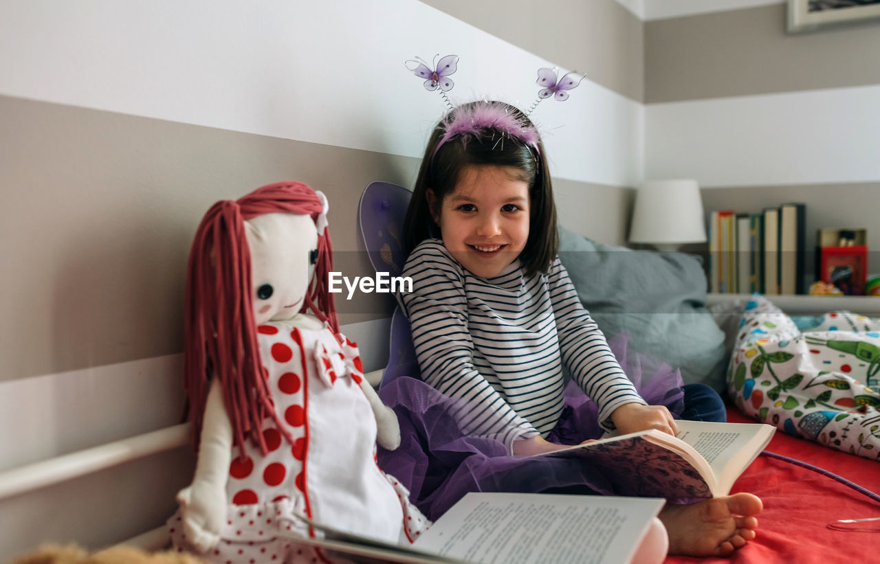 Portrait Of Smiling Girl Wearing Fairy Costume While Sitting With Book On Bed At Home