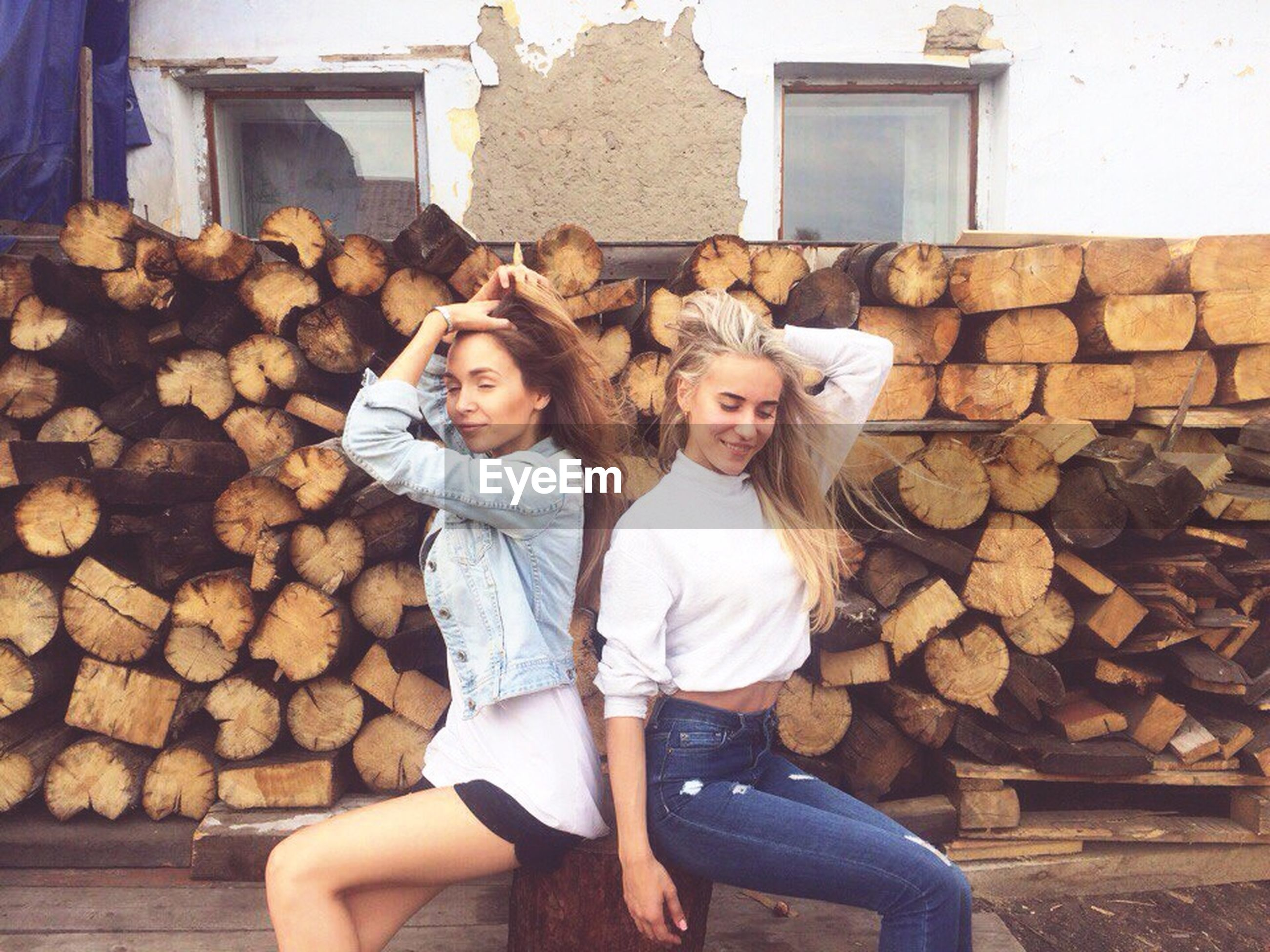 stack, log, woodpile, pile, happiness, deforestation, timber, day, casual clothing, lumber industry, young women, looking at camera, young adult, outdoors, building exterior, lifestyles, portrait, wood - material, leisure activity, real people, smiling, standing, built structure, two people, togetherness, architecture, nature