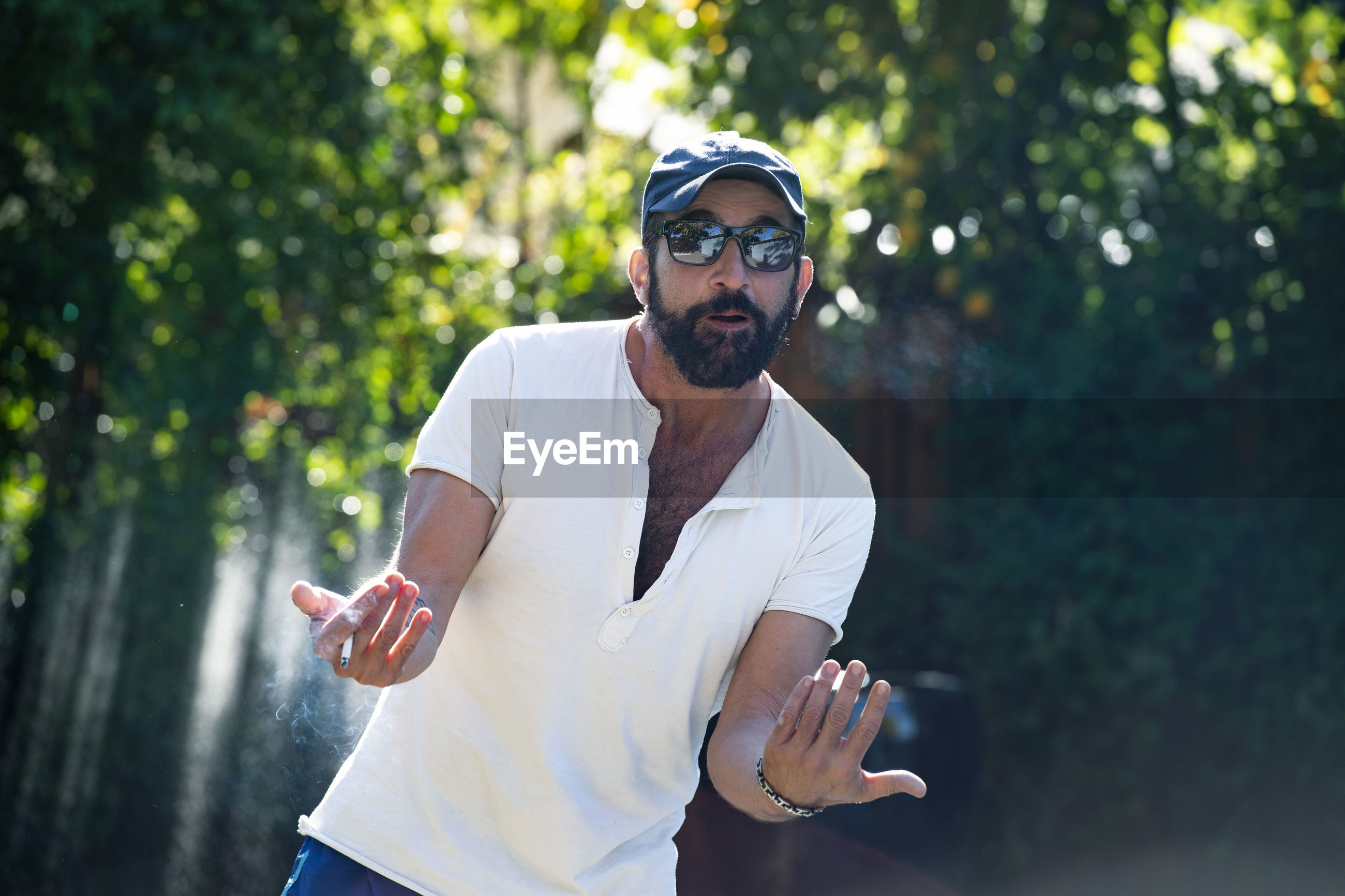 Man wearing sunglasses smoking cigarette against trees