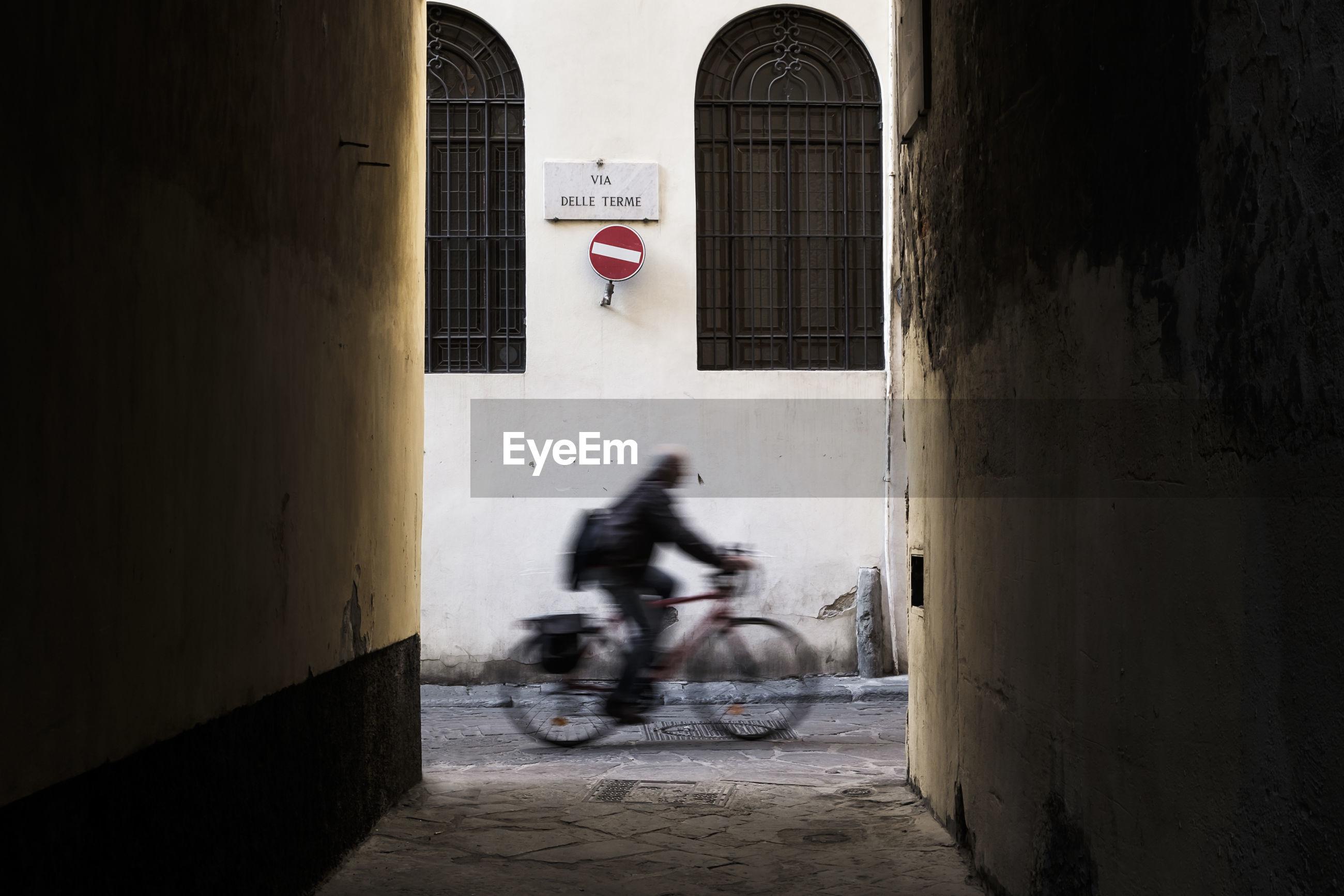 Full length of man on bike in city