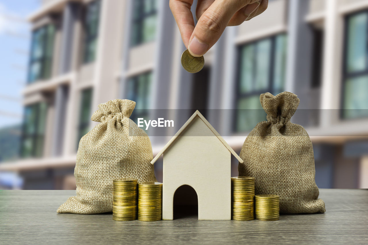 Cropped hand of person holding coin over model home by sacks and stack