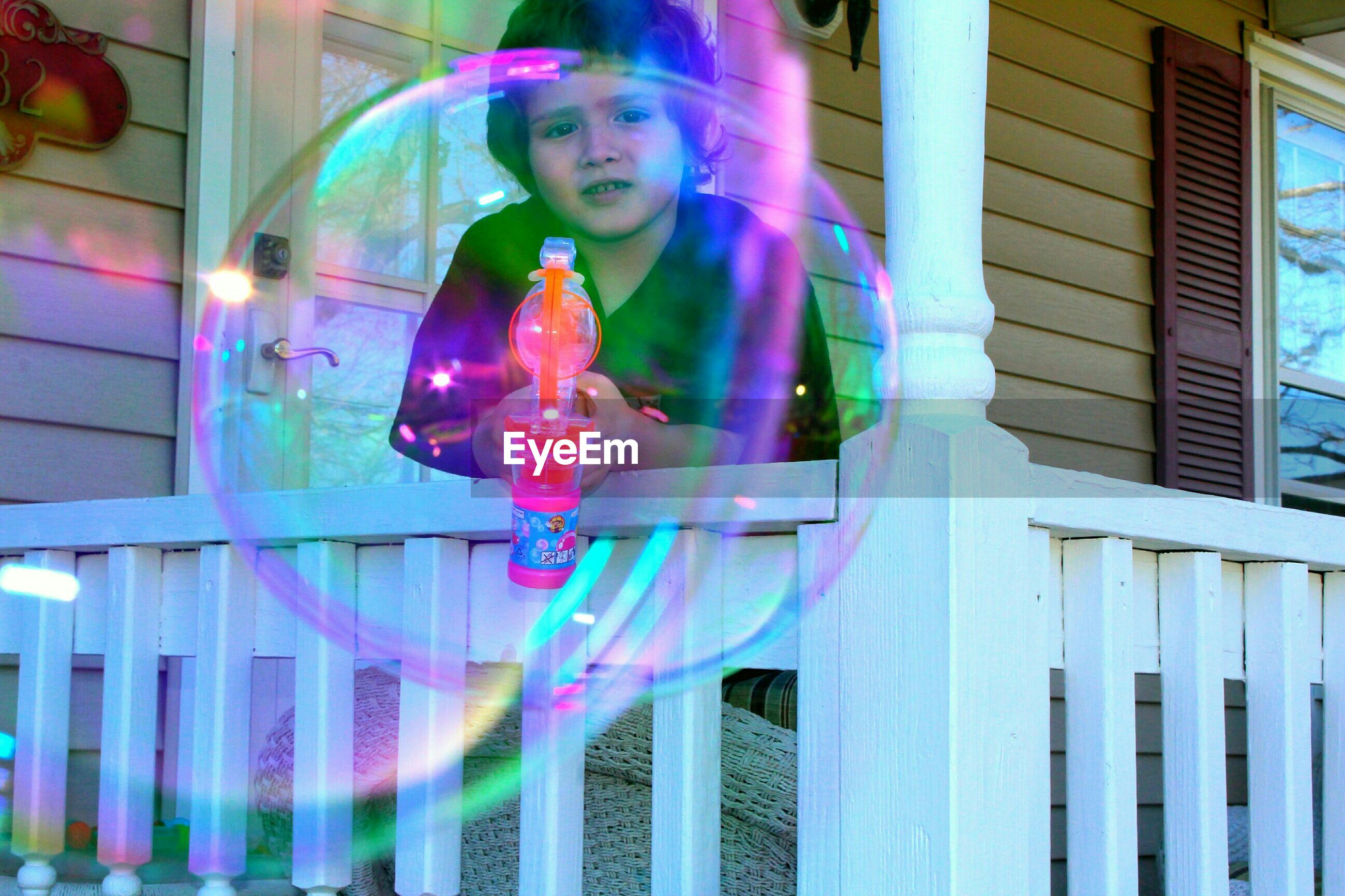 Portrait of boy holding bubble gun seen through bubbles