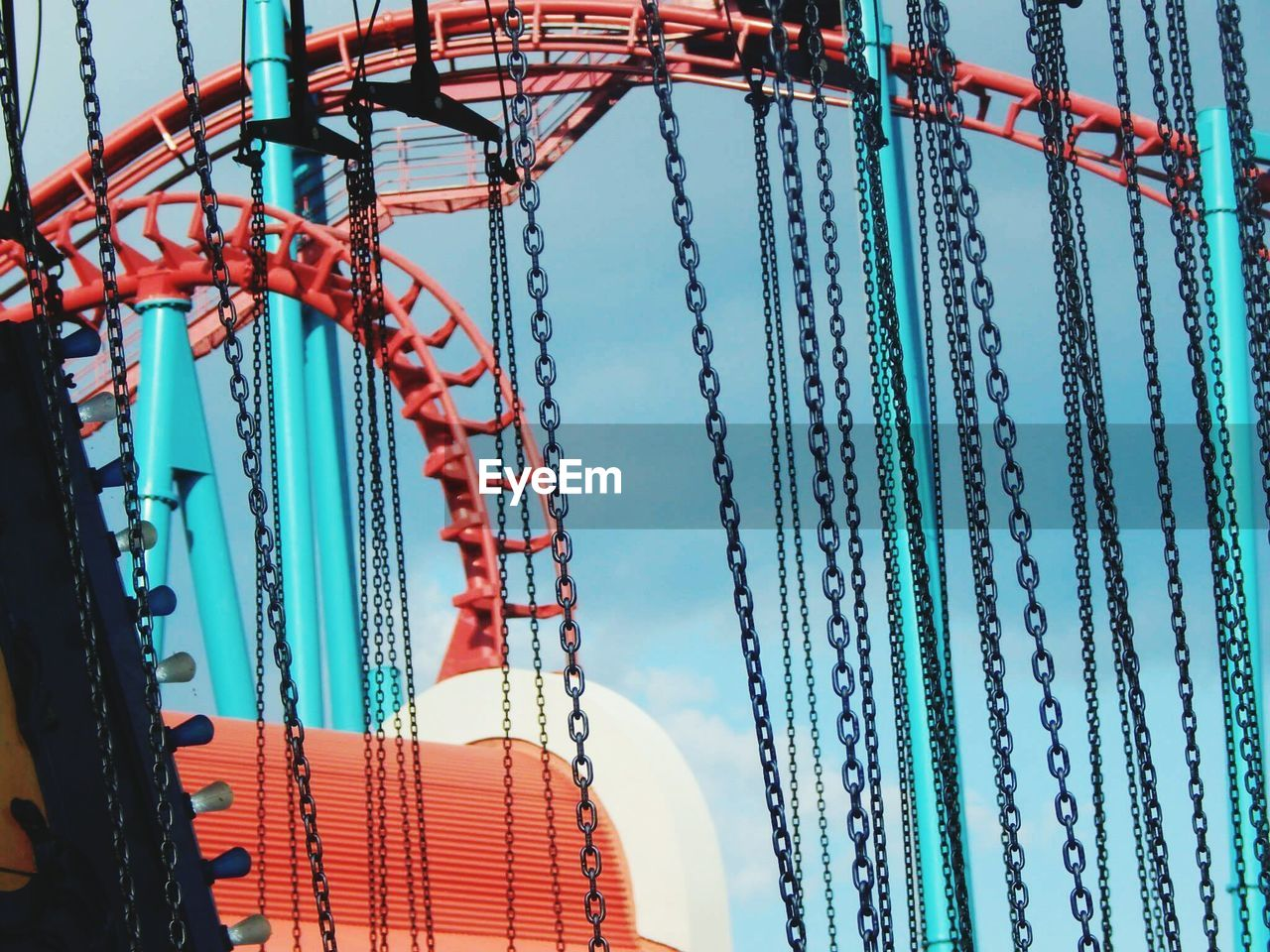 Low Angle View Of Rollercoaster And Chains Against Blue Sky