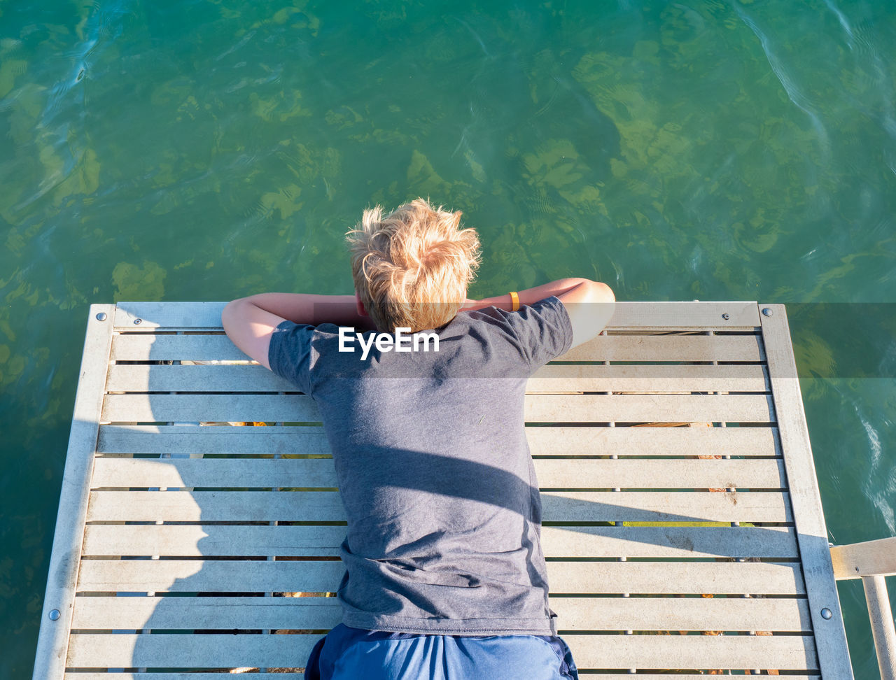 Boy lies on the mole and watches the fish in the lake water below. the joys of childhood