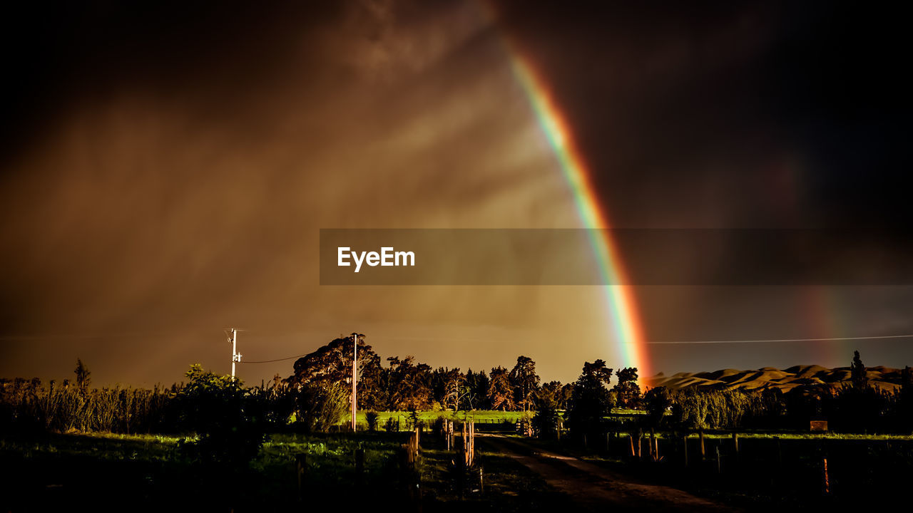Scenic view of rainbow over field at night