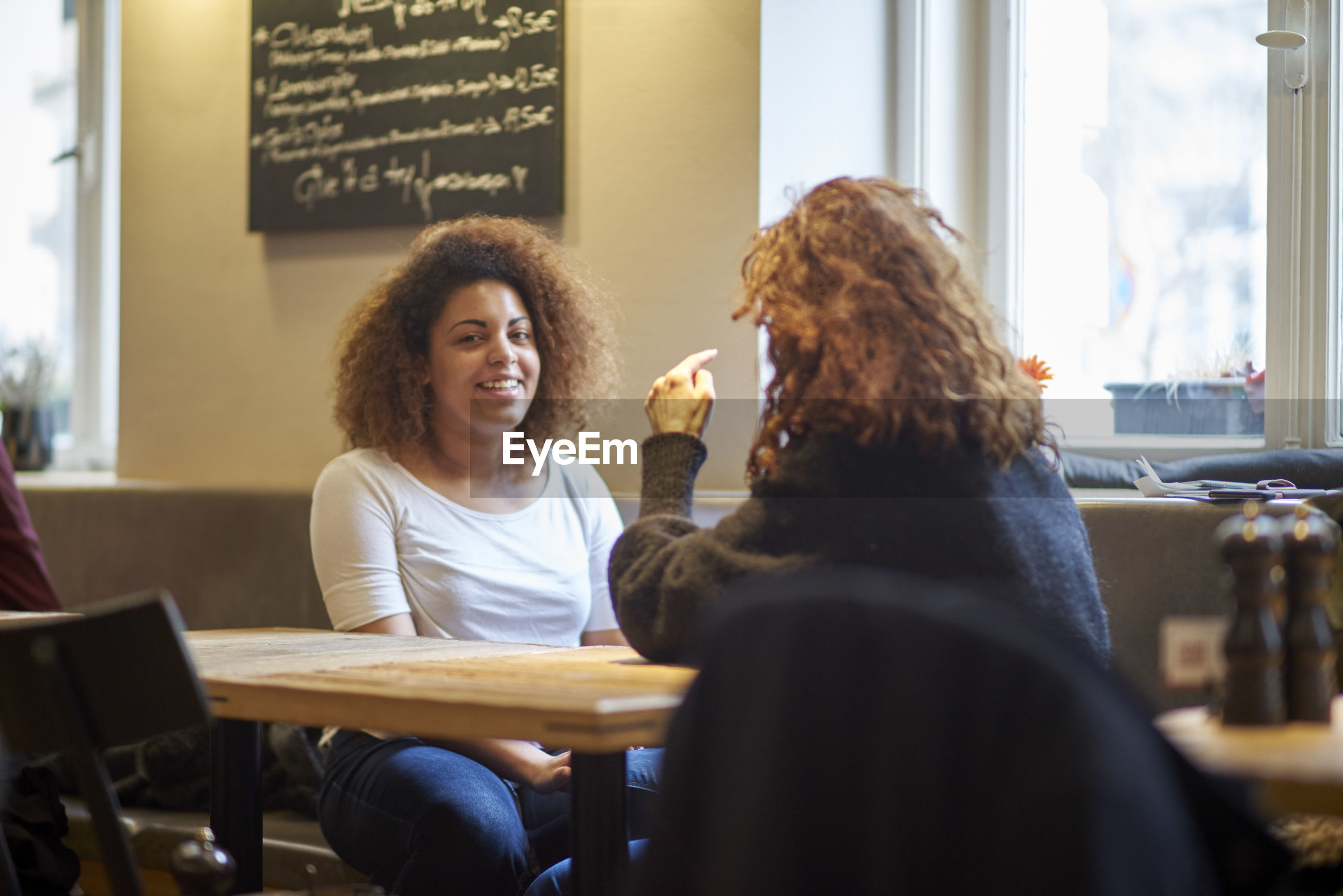 Friends talking while sitting at table in restaurant