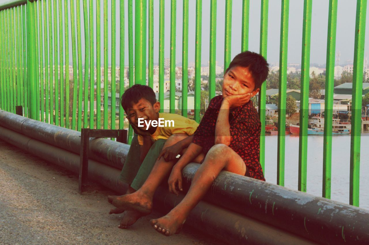Portrait Of Boys Sitting On Pipe By Railing
