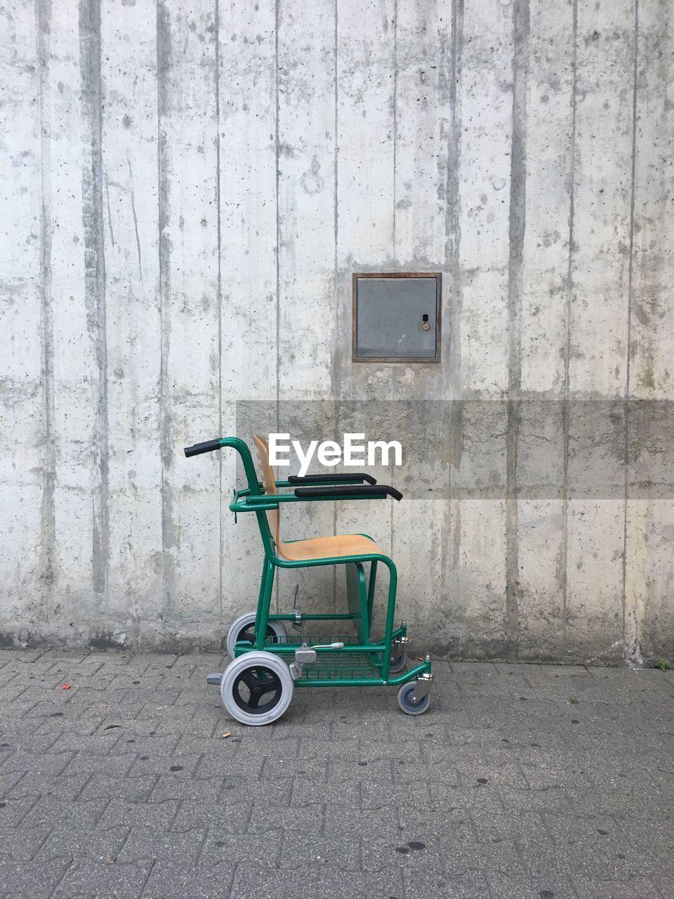 Empty wheelchair against wall