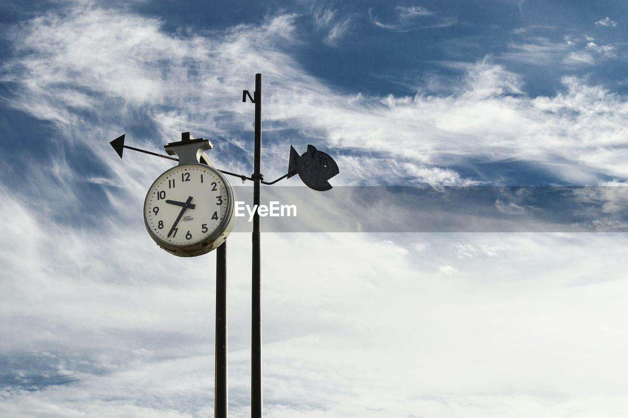 cloud - sky, sky, clock, low angle view, time, no people, pole, nature, day, lighting equipment, communication, outdoors, animal themes, weather vane, guidance, metal, animal, direction, instrument of time, animal wildlife, minute hand, meteorology
