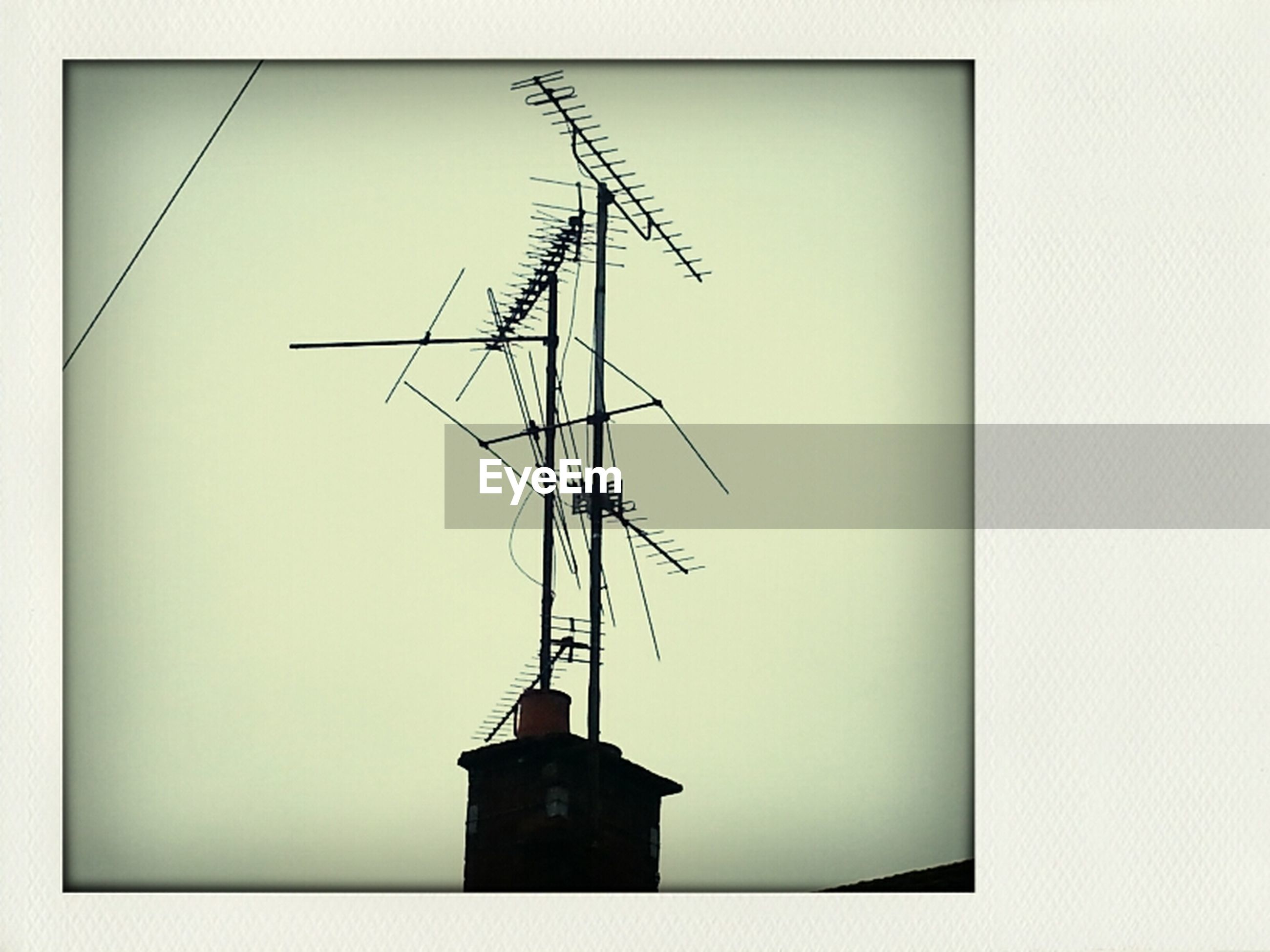 low angle view, clear sky, copy space, technology, built structure, fuel and power generation, architecture, building exterior, auto post production filter, transfer print, electricity, power supply, no people, power line, communication, outdoors, day, crane - construction machinery, sky, electricity pylon
