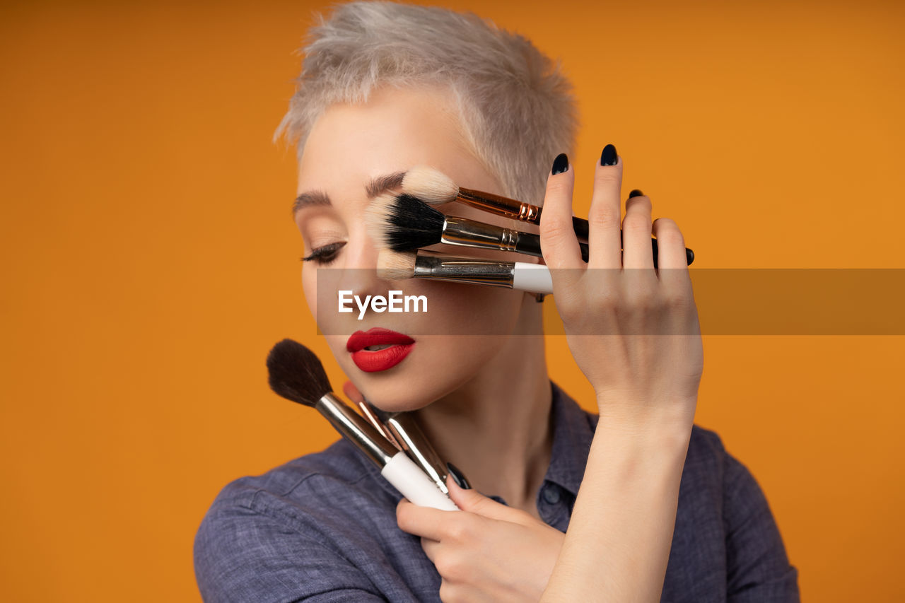 Thoughtful young woman with make-up brushes standing against orange background
