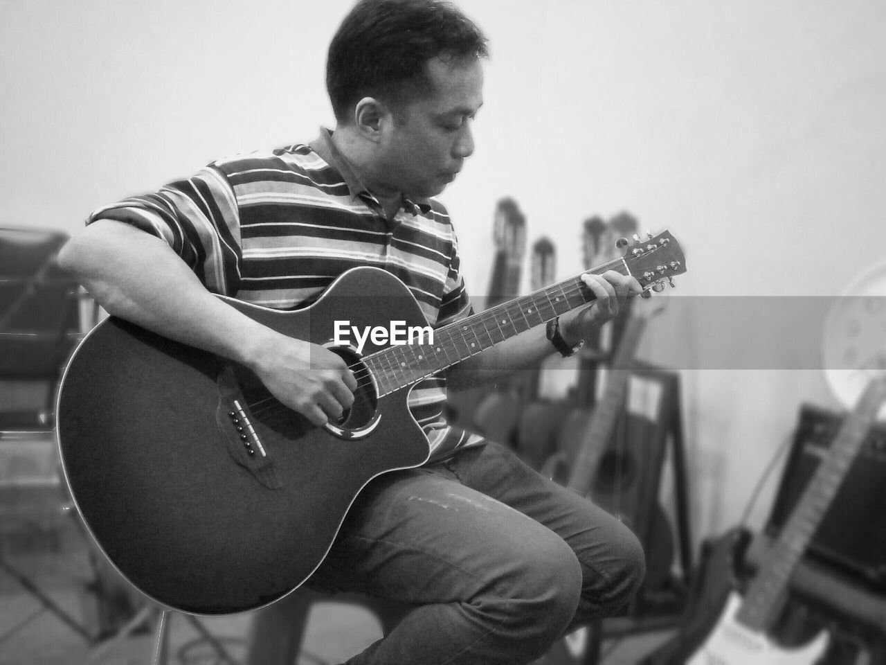 Mature man playing guitar while sitting on chair against wall