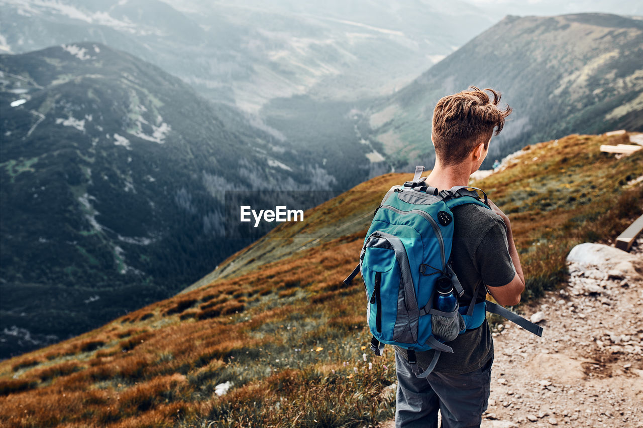 Young man with backpack hiking in a mountains, actively spending summer vacation