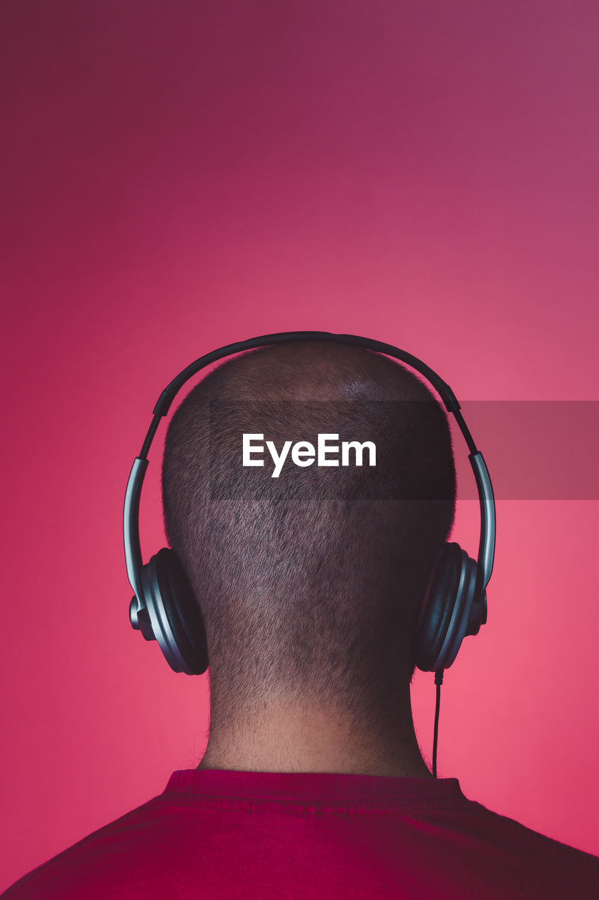 Rear view of man listening music against red background