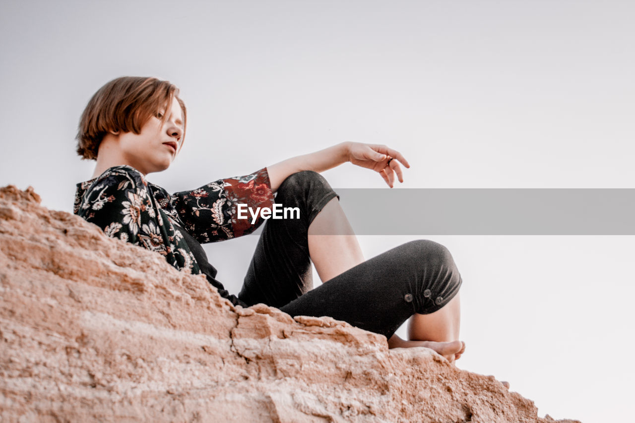 Low angle view of man sitting on sand against sky