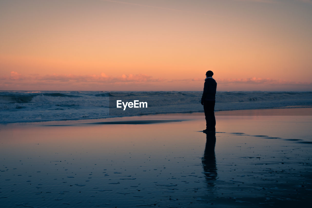 Silhouette Man Standing At Beach Against Orange Sky