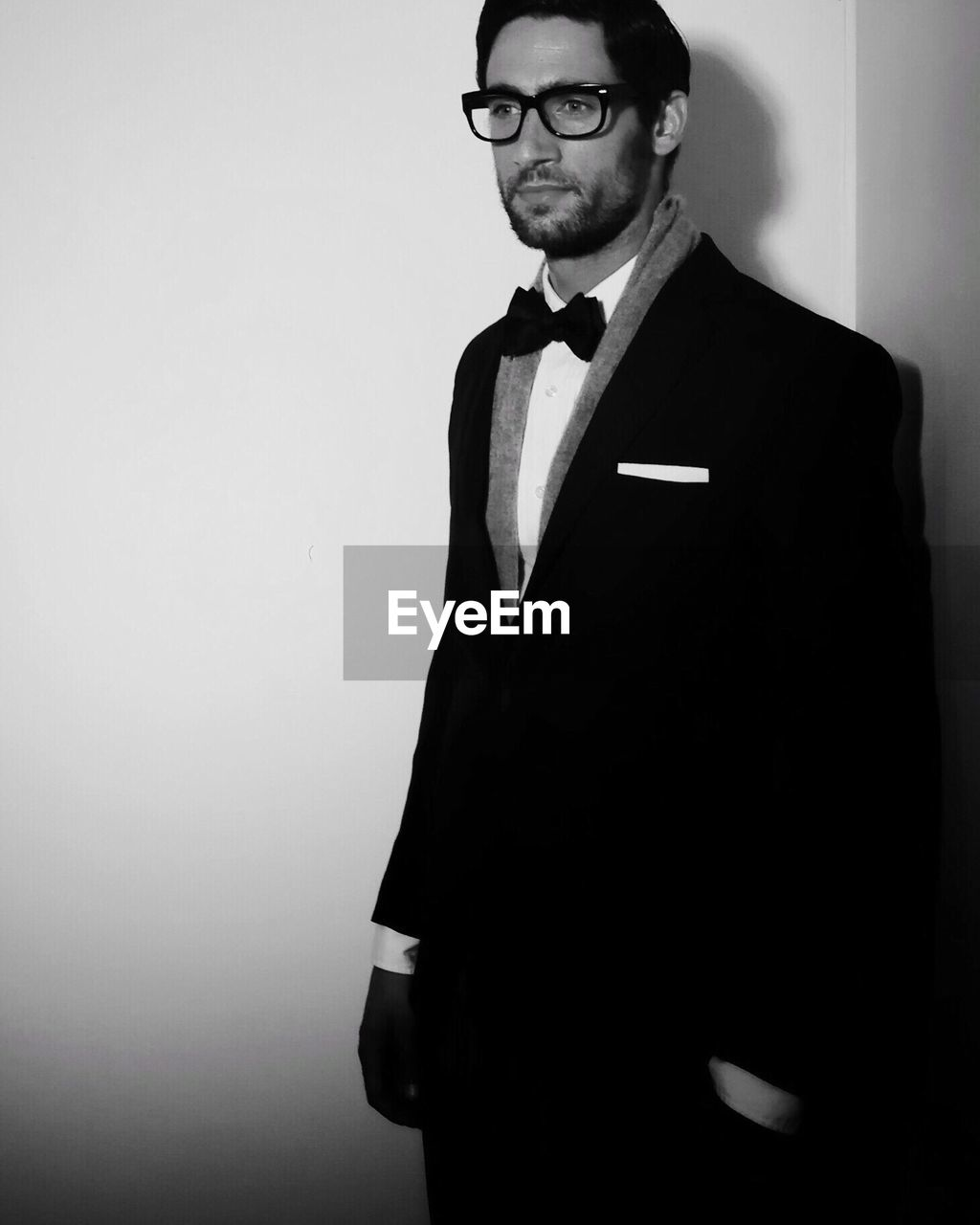 one person, standing, indoors, bow tie, clothing, young adult, studio shot, young men, portrait, front view, well-dressed, looking at camera, formalwear, glasses, wall - building feature, lifestyles, white background, beard, menswear