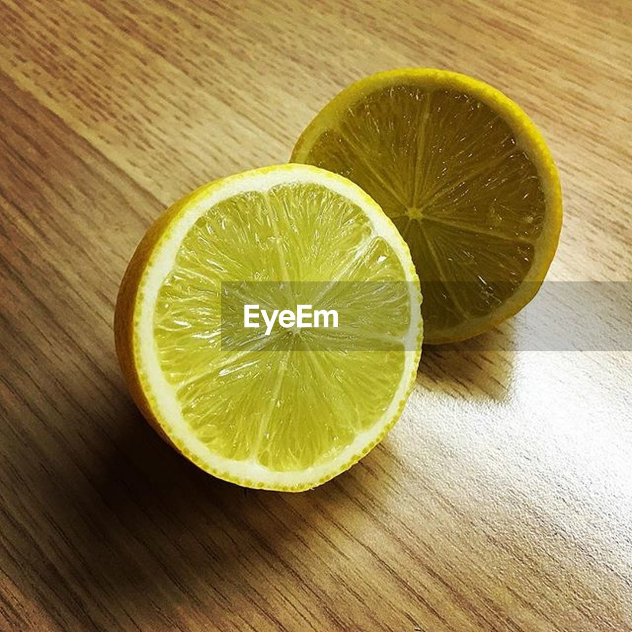 fruit, food and drink, citrus fruit, food, slice, healthy eating, freshness, lemon, wellbeing, cross section, close-up, no people, indoors, wood - material, lime, table, yellow, halved, green color, directly above, antioxidant, small group of objects, wood grain, sour taste