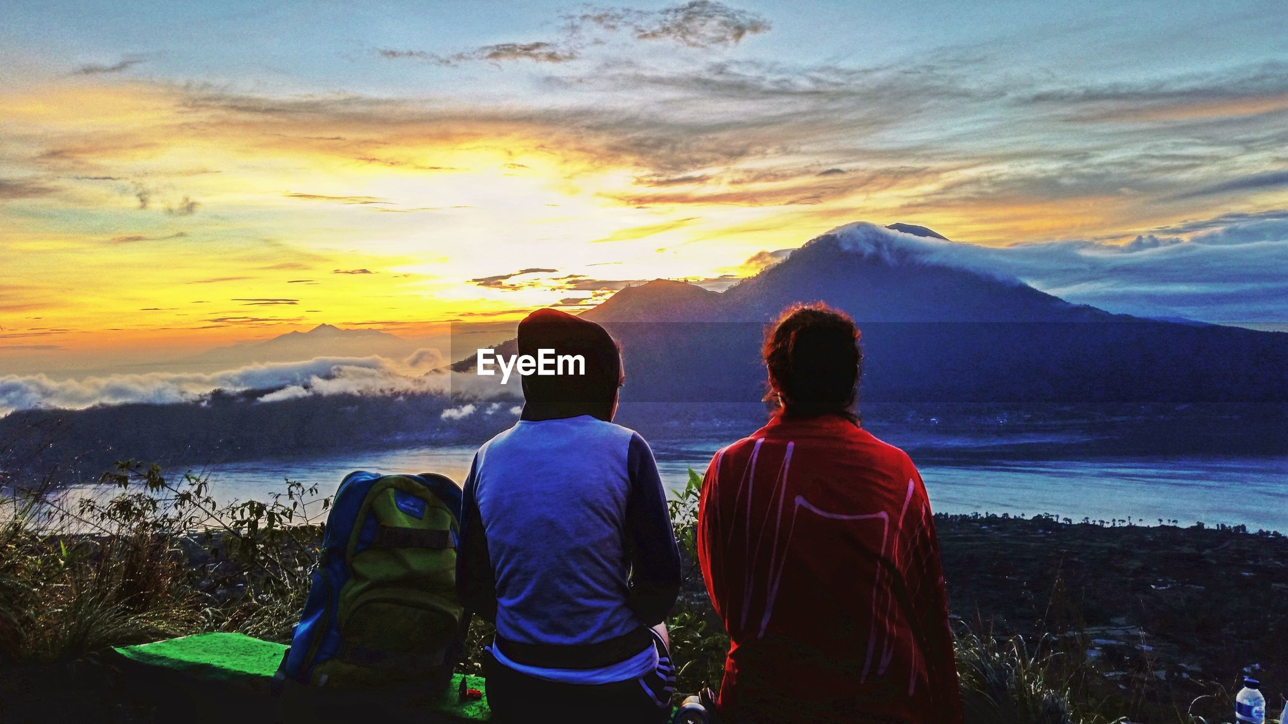REAR VIEW OF MEN ON MOUNTAIN DURING SUNSET