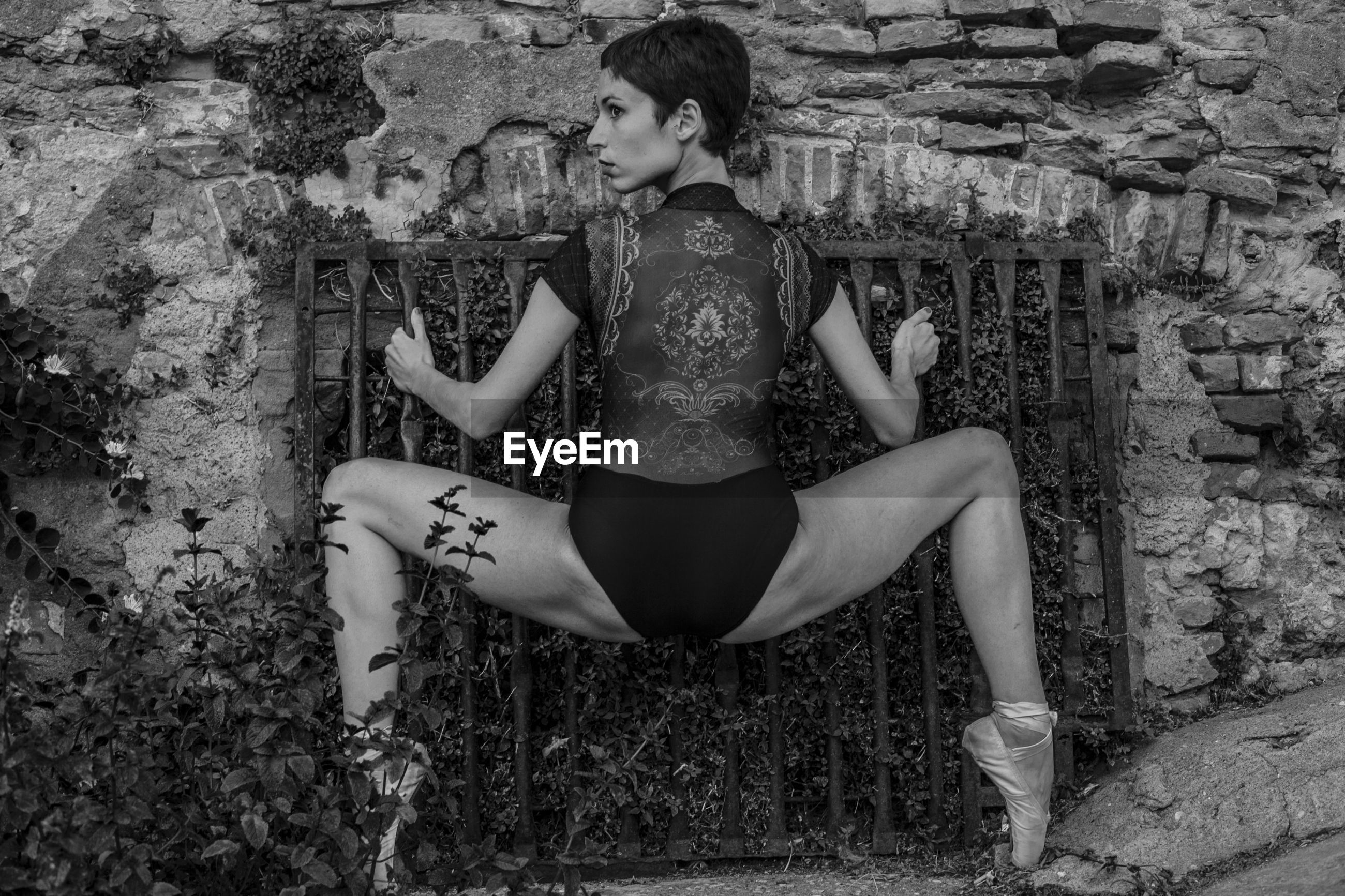 Rear view of ballerina with legs apart crouching while holding gate