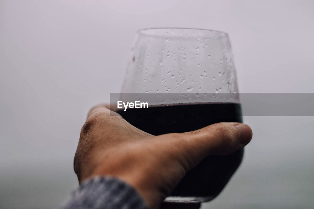 Close-up of hand holding drink against sky