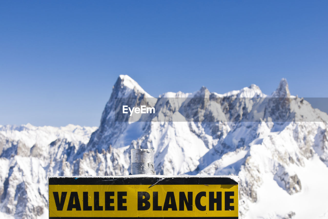 text, western script, communication, winter, cold temperature, sky, snow, sign, nature, clear sky, copy space, mountain, no people, scenics - nature, information, yellow, beauty in nature, day, information sign, snowcapped mountain, mountain peak