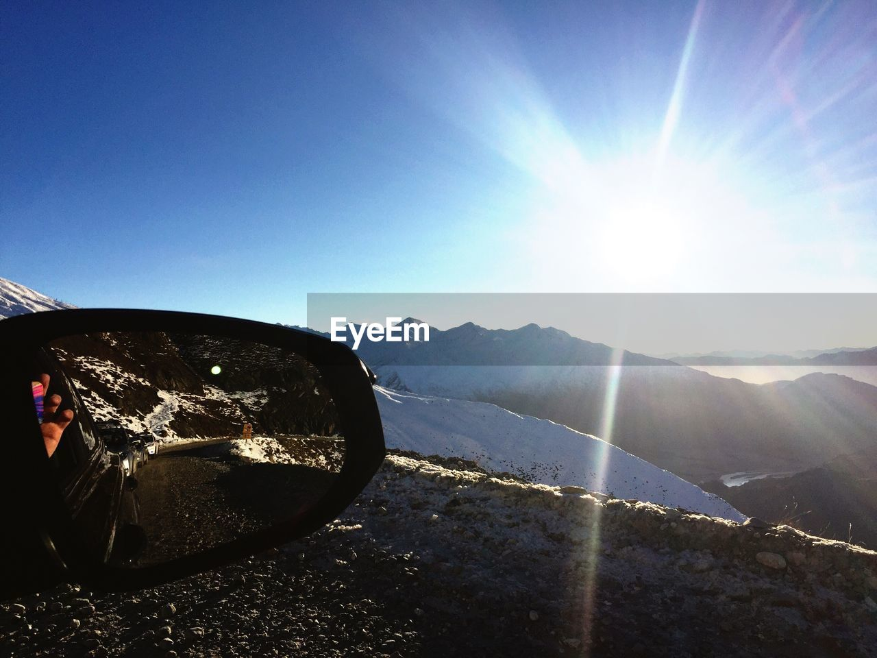 sunbeam, lens flare, sunlight, car, sun, transportation, mountain, reflection, land vehicle, side-view mirror, day, mode of transport, vehicle mirror, landscape, road trip, outdoors, no people, mountain range, nature, scenics, road, beauty in nature, sky