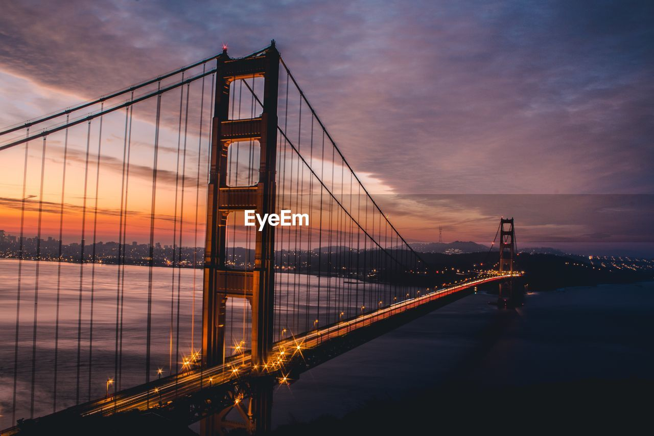 Golden Gate Bridge Over River Against Cloudy Sky During Sunset