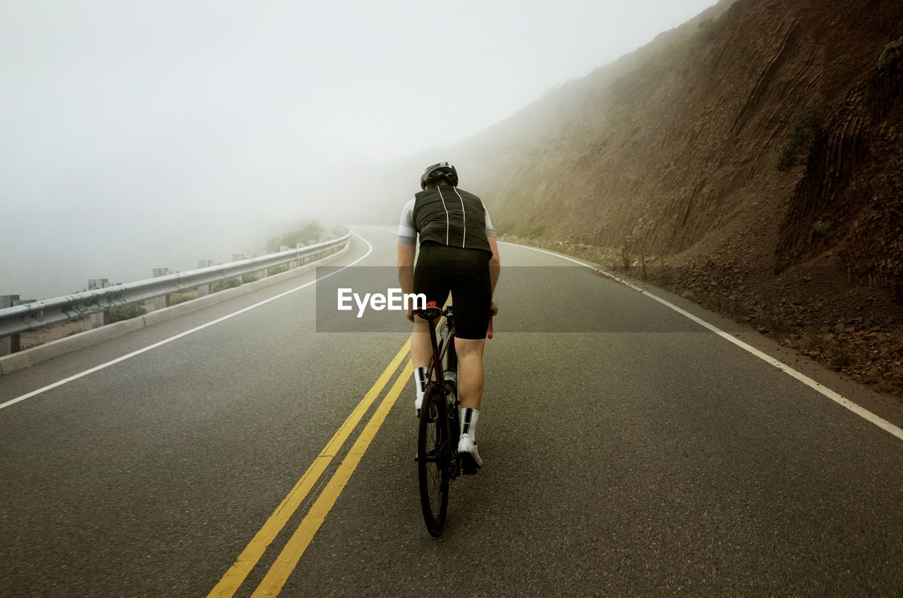 REAR VIEW OF MAN RIDING BICYCLE ON ROAD AGAINST MOUNTAIN
