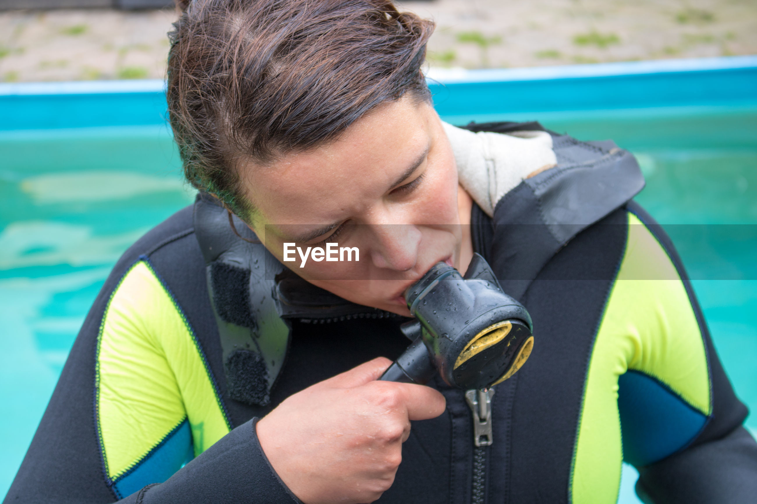 Woman checking aqualung at poolside