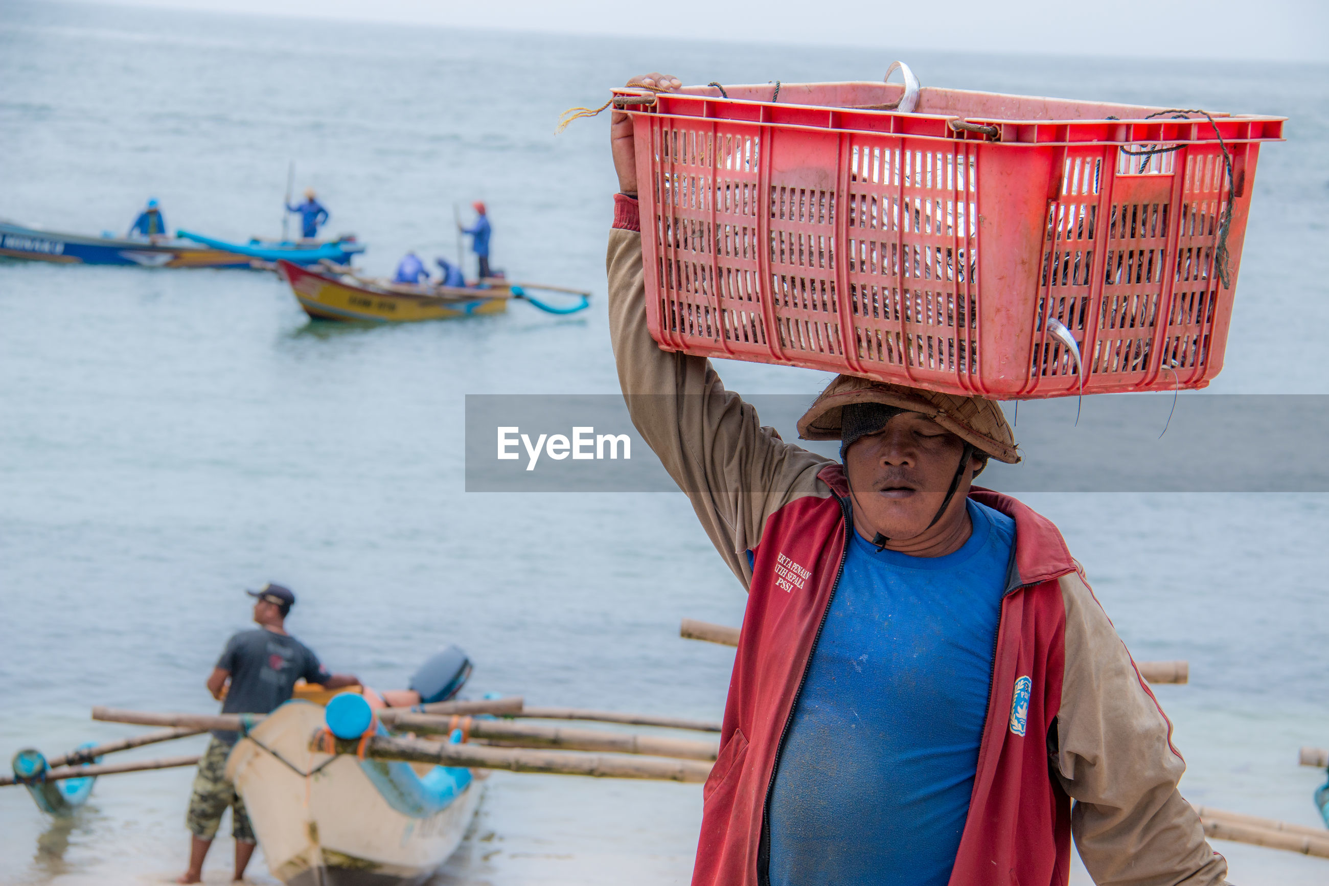 Man carrying crate while walking against sea