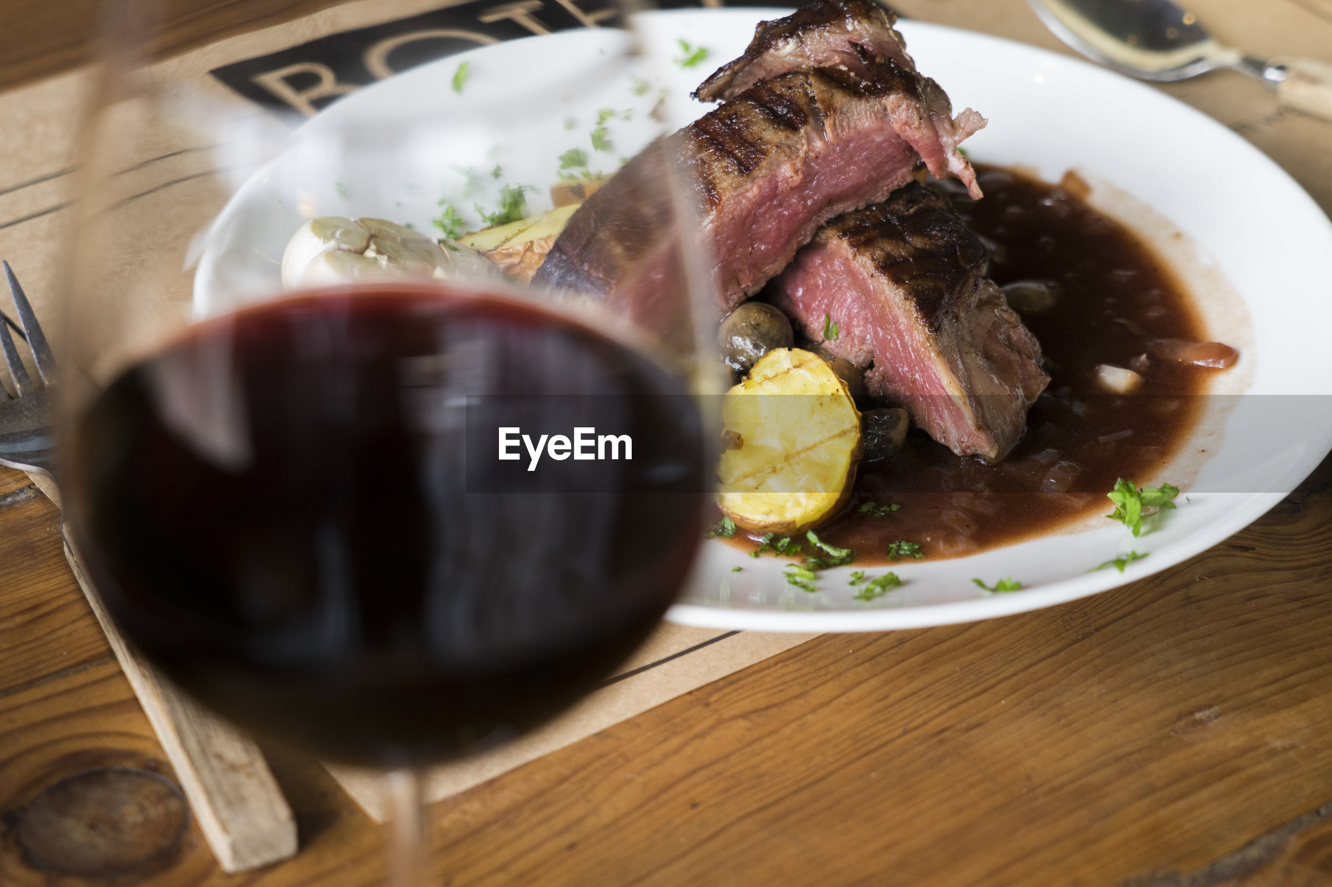 High angle view of beef steak and red wine served on table