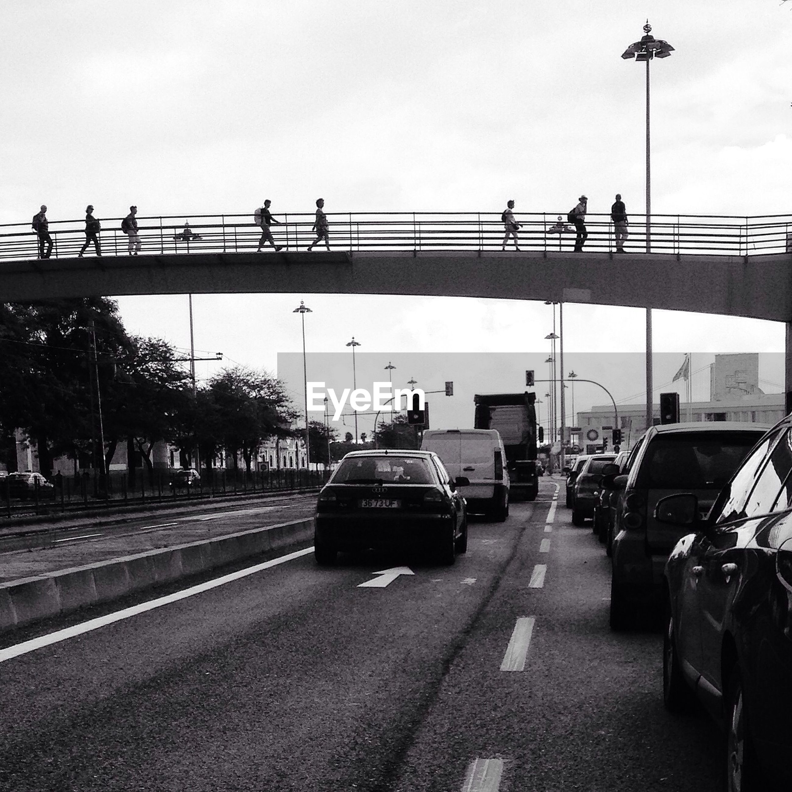 People walking on bridge over city street