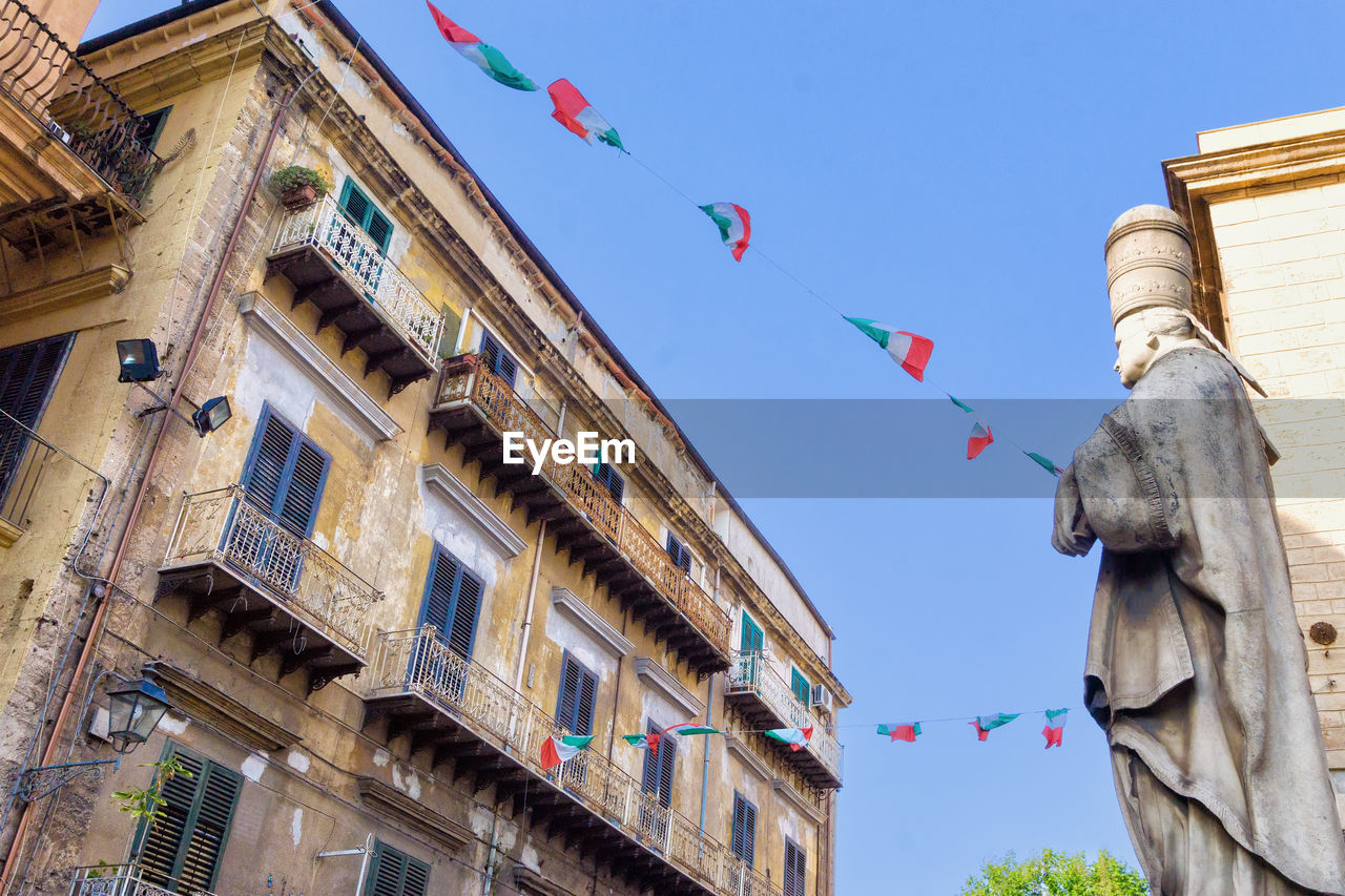 architecture, low angle view, building exterior, built structure, sky, flag, building, nature, no people, day, clear sky, multi colored, decoration, hanging, outdoors, the past, bunting, history, blue, art and craft