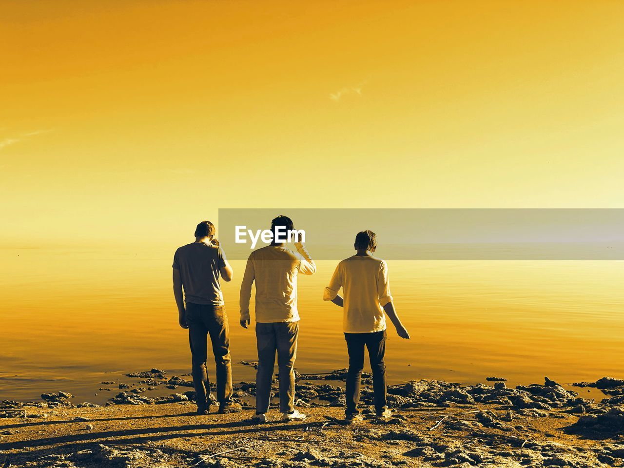 sky, sunset, beauty in nature, leisure activity, rear view, men, orange color, real people, lifestyles, togetherness, nature, water, standing, scenics - nature, group of people, full length, bonding, land, friendship, outdoors, horizon over water
