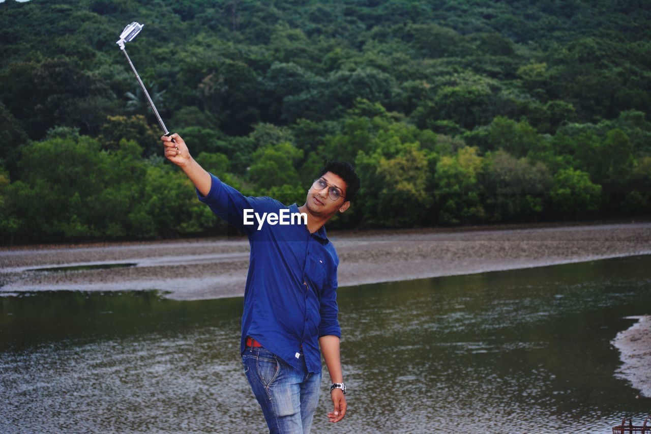 real people, water, one person, casual clothing, leisure activity, mid adult, three quarter length, standing, young adult, mid adult men, looking at camera, holding, lake, portrait, front view, lifestyles, outdoors, smiling, happiness, tree, young women, day, nature, selfie, people