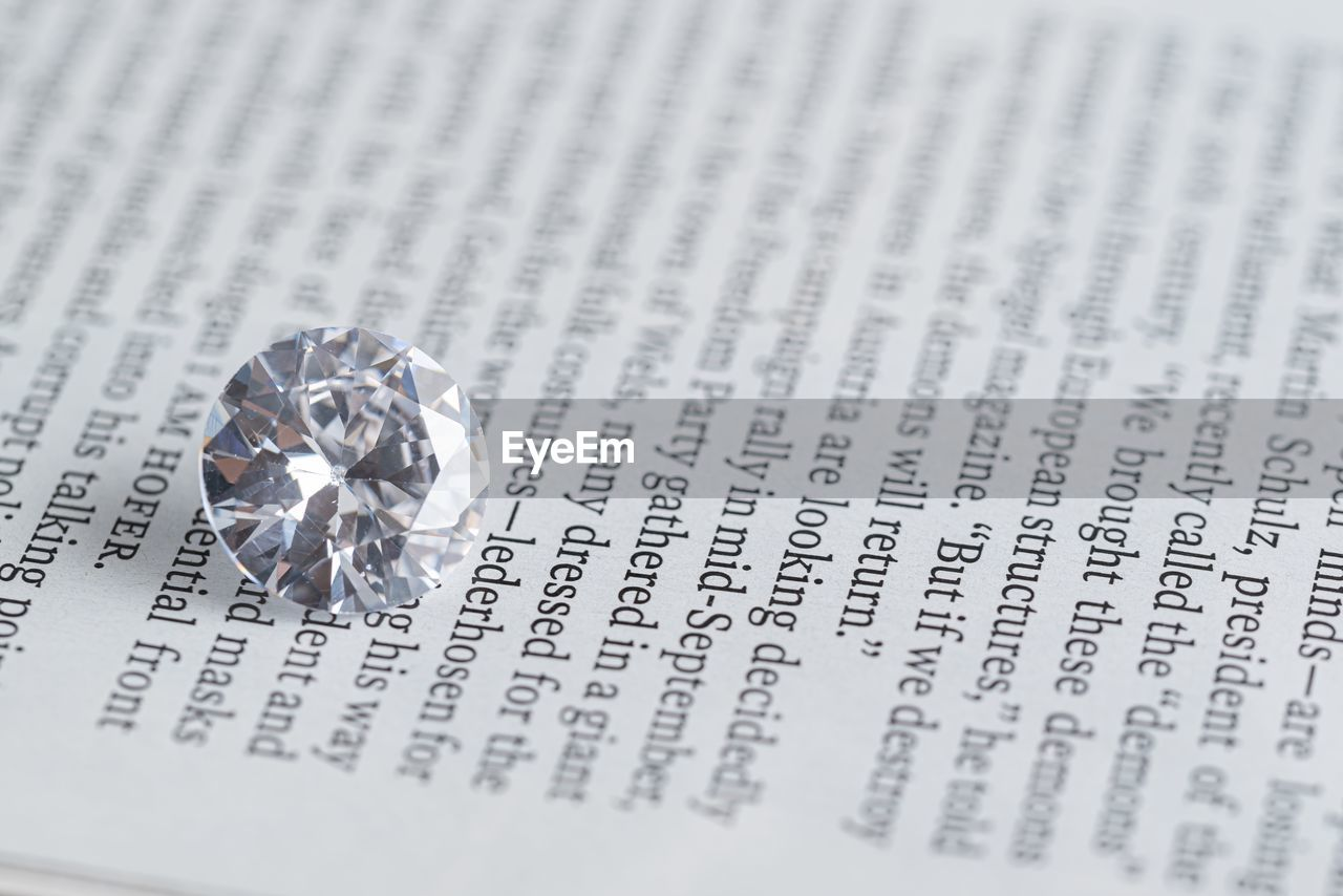 diamond - gemstone, jewelry, text, selective focus, wealth, event, indoors, celebration, ring, close-up, western script, wedding, emotion, paper, no people, love, studio shot, communication, business, still life, luxury, silver colored, valentine's day - holiday