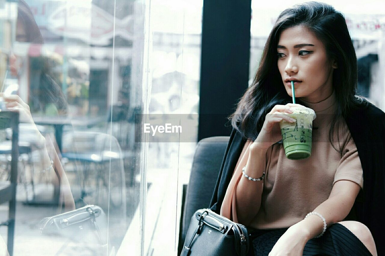Beautiful woman drinking while looking through window at cafe
