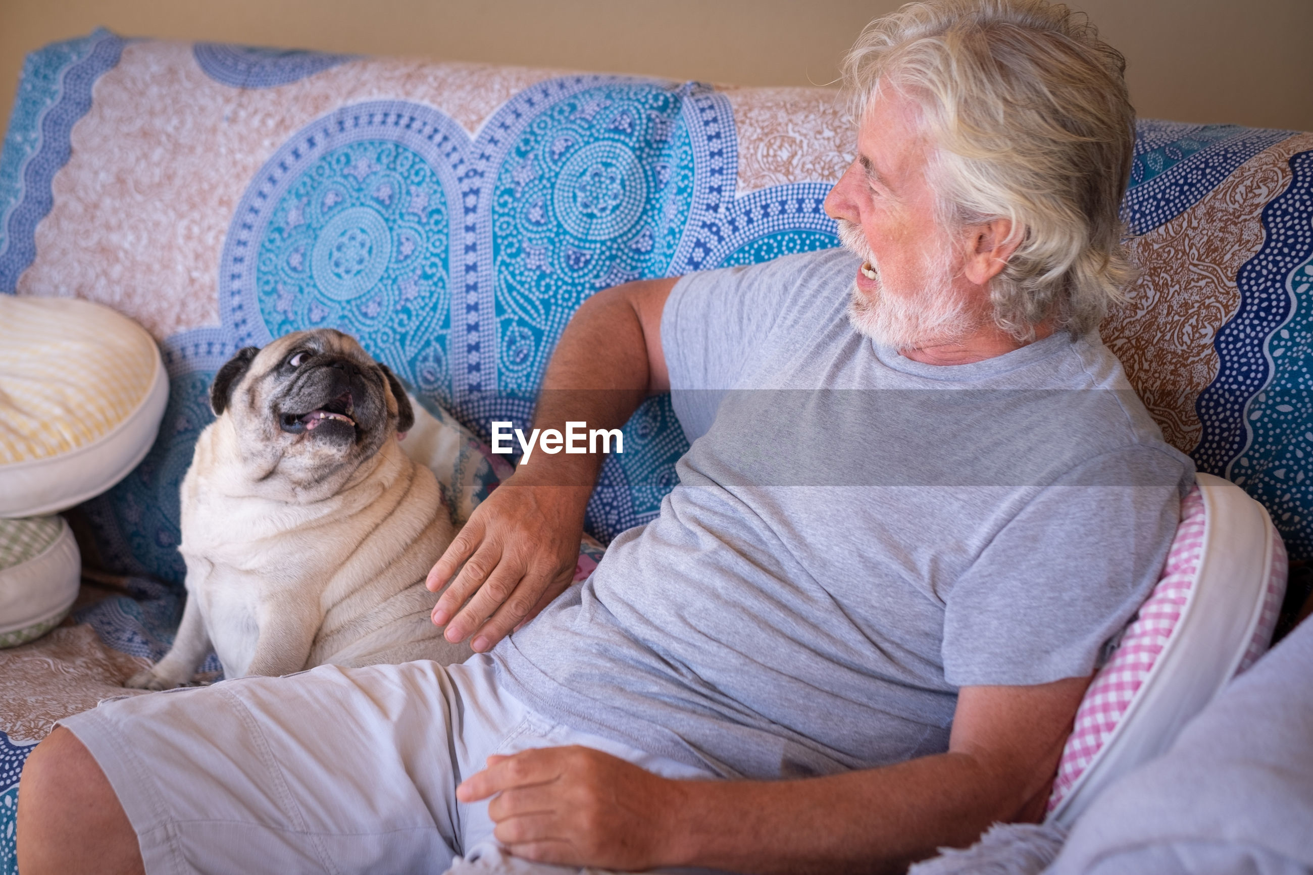 Senior man with pug sitting on sofa at home