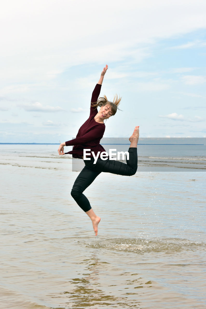Mid Adult Woman Jumping On Shore Against Sky