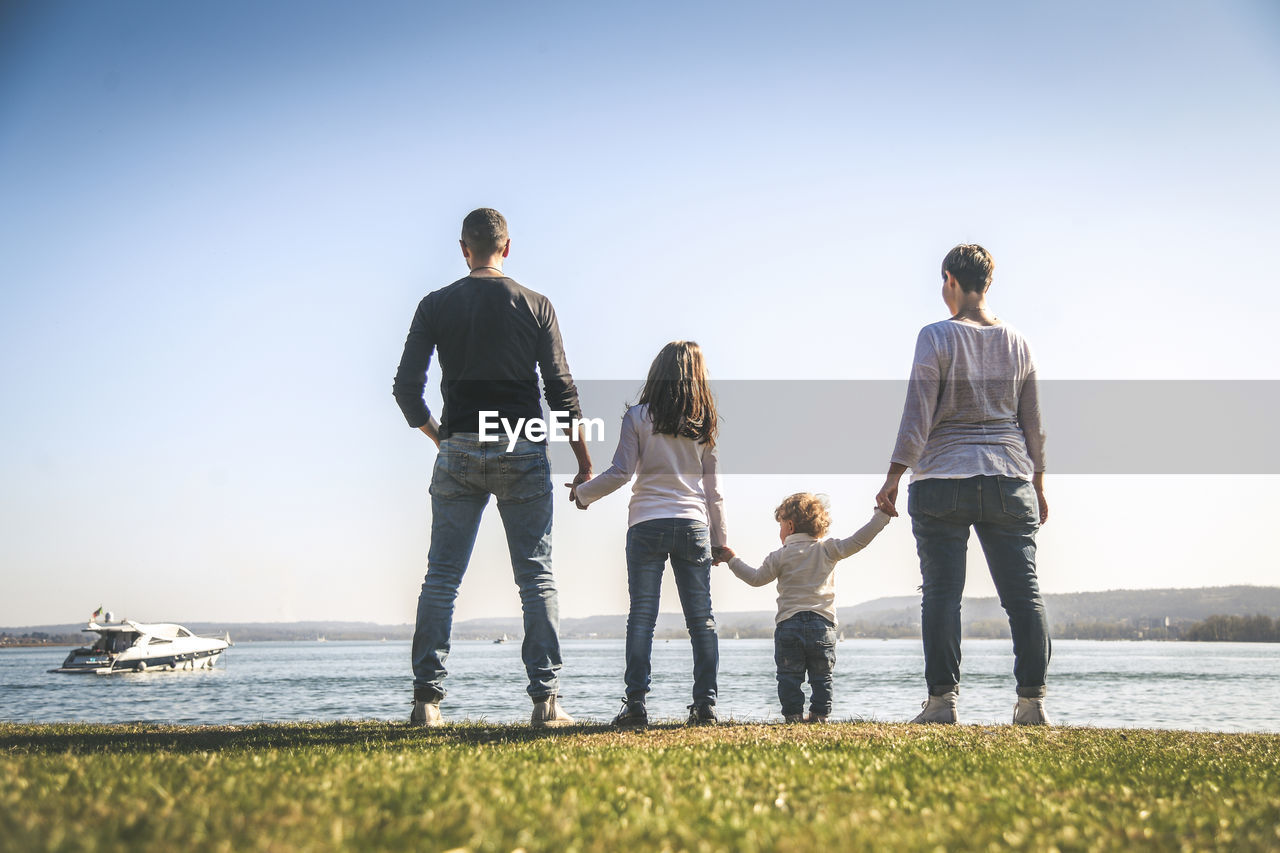 family, togetherness, group of people, sky, women, real people, men, child, casual clothing, water, leisure activity, females, childhood, nature, father, boys, rear view, full length, parent, males, sister, son, daughter, positive emotion, outdoors