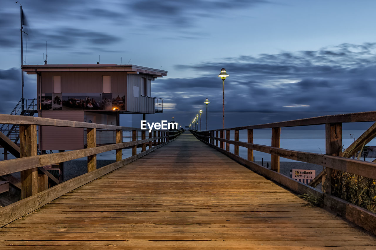 direction, the way forward, built structure, sky, architecture, railing, illuminated, cloud - sky, nature, wood - material, no people, diminishing perspective, bridge, lighting equipment, connection, street light, dusk, bridge - man made structure, pier, water, outdoors, wood paneling, long