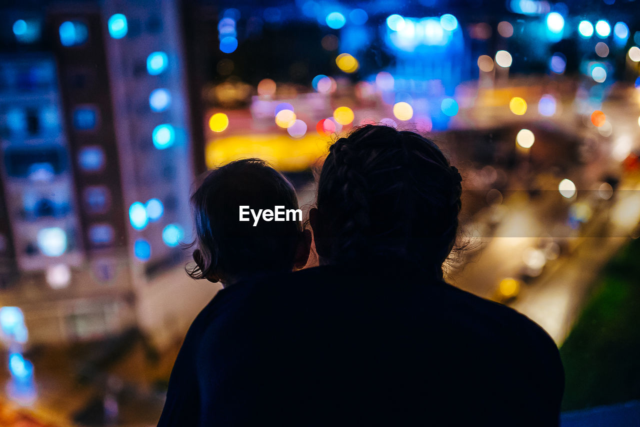 Rear View Of Silhouette Mother With Son In Illuminated City At Night