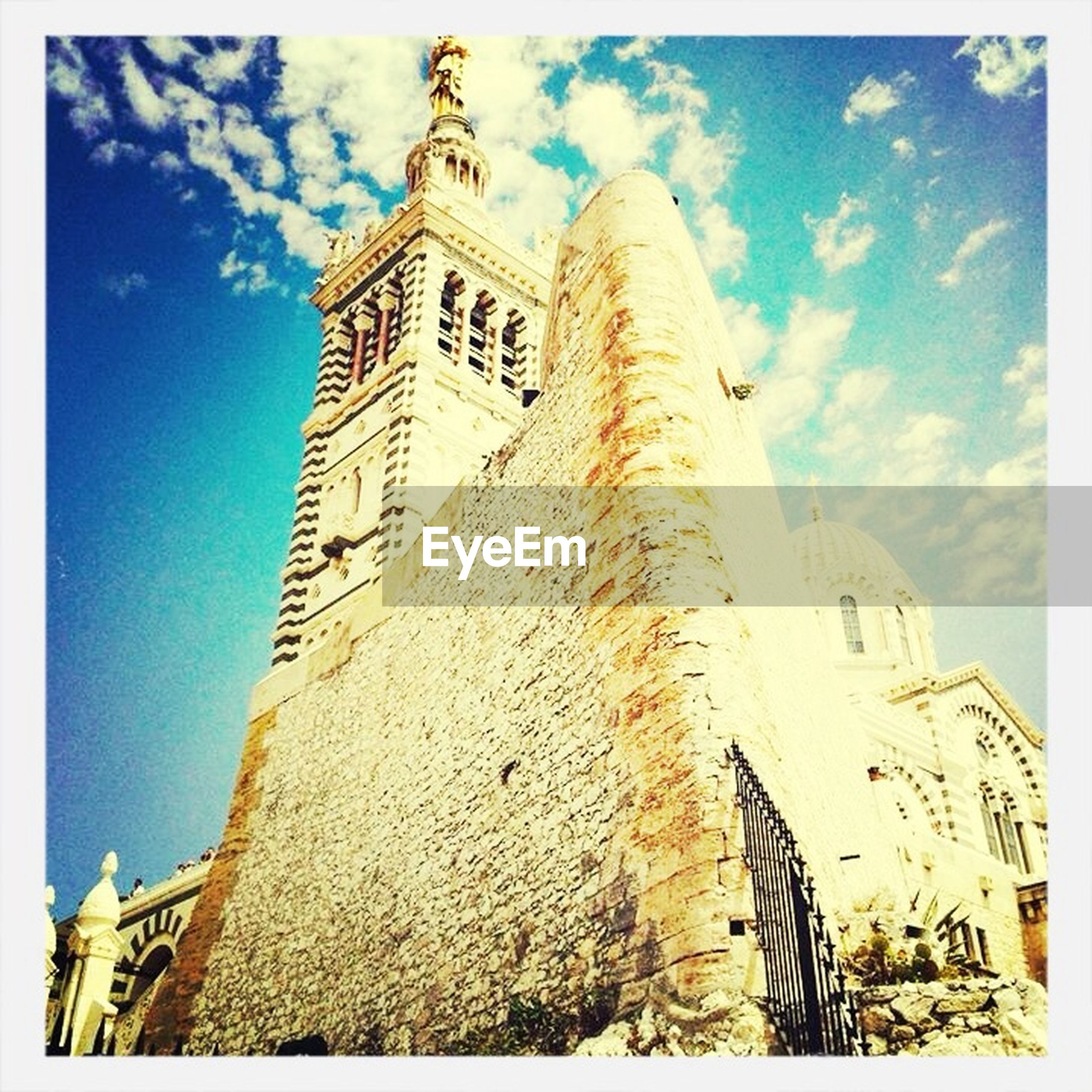 building exterior, architecture, built structure, low angle view, sky, transfer print, church, blue, religion, place of worship, tower, auto post production filter, spirituality, cathedral, history, clock tower, famous place, cloud - sky