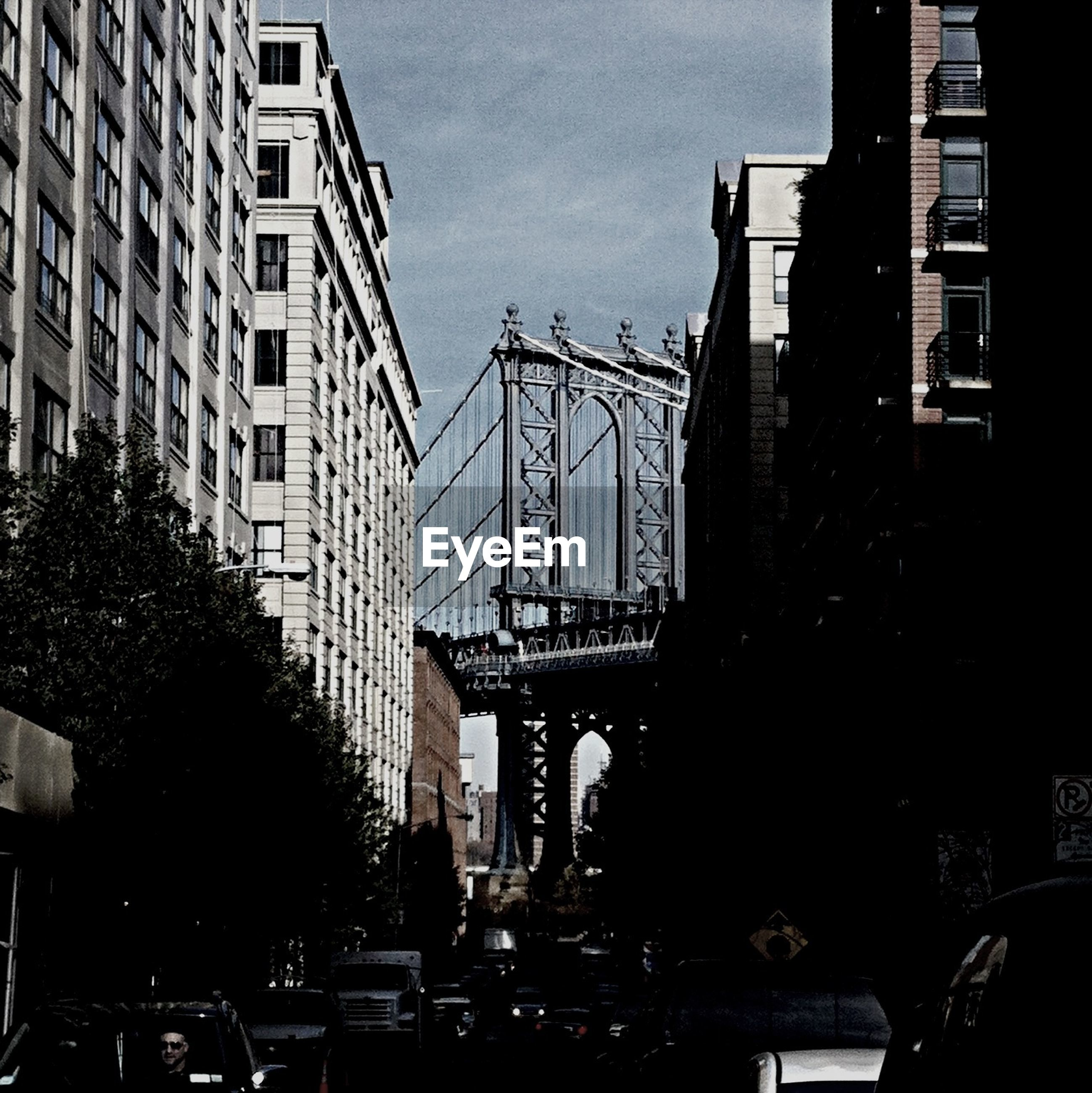 Low angle view of buildings against bridge in city